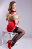 Pin up girl in red dress sitting on the chair Royalty Free Stock Photography