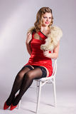 Pin up girl in red dress sitting on the chair Stock Image