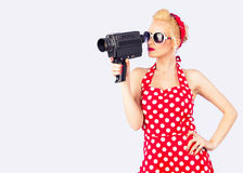 Pin-up girl with red vintage dress holding vintage 8 mm camera Royalty Free Stock Photos