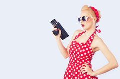 Pin-up girl with red vintage dress holding vintage 8 mm camera Royalty Free Stock Photo