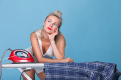 Pin up girl retro style portrait woman ironing. Posing housewife with iron blue background royalty free stock photography