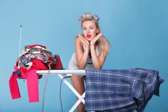 Pin up girl retro style portrait woman ironing. Posing housewife with iron blue background Royalty Free Stock Images