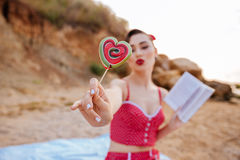 Pin up girl showing heart shaped candy at the beach Royalty Free Stock Photography