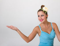 Pin-up girl showing something on palm of hand Royalty Free Stock Images