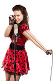 Pin-up girl singing a song. Pin-up girl with a microphone on stage singing a song royalty free stock photography