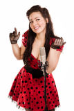 Pin-up girl singing a song. Pin-up girl with a microphone on stage singing a song Stock Photo