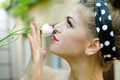 Pin-up girl smells a roses flower. Young girl smells a roses flower Royalty Free Stock Image