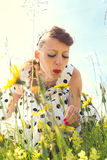 Pin up Girl with a suicide roll on a wildflower meadow with back Royalty Free Stock Photo