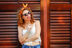 Pin-up girl in sunglasses licking lollipop. Stock Photo