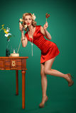 Pin-up girl talking on retro phone and holding a lollipop. Pin-up girl in a short red dress in a characteristic pose Royalty Free Stock Photography