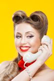 Pin-up girl talking on retro telephone Stock Photos
