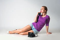 Pin up girl talking by vintage phone Stock Images