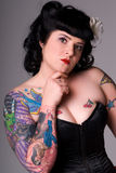 Pin-up girl with tattoos. Portrait of a woman with Pin-up style hair and make-up, wearing a black satin corset. She is holding one hand up to her chin, and she royalty free stock images