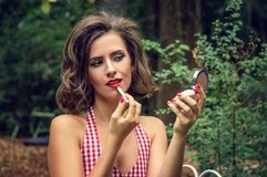 Pin-up girl tints lips with lipstick, looking in the mirror of a compact. royalty free stock image