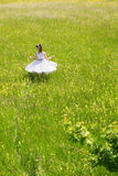 Pin up Girl is twisting in a wildflower meadow Royalty Free Stock Image