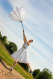 Pin up Girl with a umbrella is blowing off the path Royalty Free Stock Photos