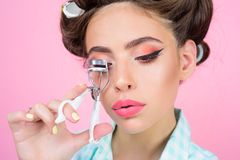 Pin up girl. vintage housewife woman curl eyelashes with tool. happy girl grooming in morning. beauty salon and stock photo