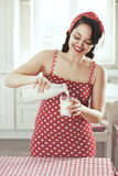 Pin up girl. Vintage retro photo of pin up girl in the kitchen at house Stock Photo