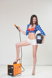 Pin-up girl with the welder. Light background Royalty Free Stock Photos