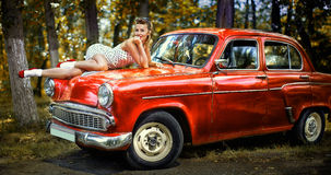 Pin-up girl in white dress on the hood of red retro car on a background of green forest royalty free stock images