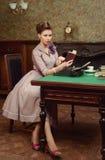 Pin Up härlig ung kvinna i inre läsning för tappning en bok och tryck på en gammal skrivmaskin Royaltyfri Bild