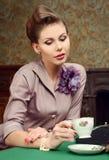 Pin Up härlig ung kvinna som dricker te i tappninginre Arkivfoto