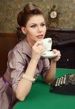 Pin Up härlig ung kvinna som dricker te i tappninginre Arkivfoton