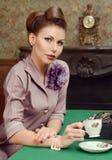 Pin Up härlig ung kvinna som dricker te i tappninginre Fotografering för Bildbyråer