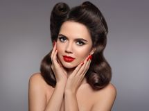 Pin up hairstyle. Beautiful 50s girl holding her cheeks with red. Lips makeup and manicured nails looking at camera. Expressive facial expressions. Beauty stock image