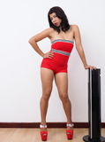 Pin-up look for pretty woman standing in front of tower fan Stock Photography
