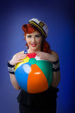 Pin up model in sailor costume isolated on blue background. Pin up model in sailor costume holding a big beach ball isolated on blue background Stock Images