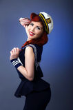 Pin up model in sailor costume isolated on blue background. Pin up model in sailor costume saluting. studio portrait over blue background Stock Photography