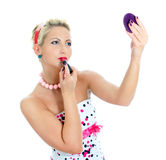 Pin-up portrait of woman applying lipstick. Stock Images