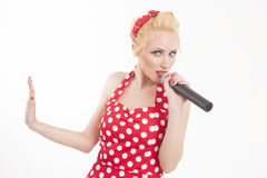 Pin-up sing star talking into a mic. Isolated portrait of a funny pin-up sing star talking into a microphone. Pop star karaoke royalty free stock images