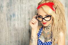 Pin-up spectacles. Close-up portrait of a modern pin-up girl wearing old-fashioned polka-dot dress and spectacles and modern dreadlocks. Fashion shot Royalty Free Stock Image