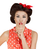 Pin-up style girl with finger on lips Stock Photography
