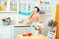 Pin-up style. Girl with a jug of flowers. Royalty Free Stock Photography
