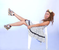 Pin-up style girl sitting on the chair Stock Photo
