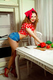 Pin up style housewife posing in the kitchen and smiling on came Stock Photos