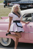Pin-up waitress. Picture of beautiful blond pin up with pink cadillac convertible Stock Photo