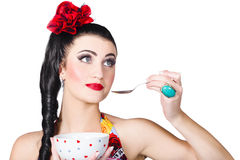 Pin-up woman eating breakfast cereal with spoon. Attractive young Italian pin-up woman eating breakfast cereal with spoon and bowl, over white background Royalty Free Stock Photo