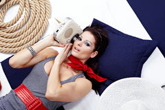 Pin-up woman laying and listening music Royalty Free Stock Image