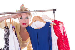 Pin-up woman looking out for shopping sale. Pinup woman looking out throuhg dresses on hanger isolated over white Royalty Free Stock Images