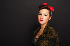 Pin-up woman with milytary jacket on black background Stock Photo