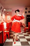 Pin up woman in red dress with white dots. Vintage style. Retro cafe interior with checkerboard  floor Stock Images