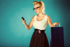 Pin up woman with shopping bag and phone. Royalty Free Stock Photo