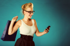Pin up woman with shopping bag and phone. Royalty Free Stock Images