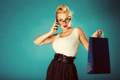Pin up woman with shopping bag and phone. Stock Photography