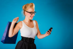 Pin up woman with shopping bag and phone. Royalty Free Stock Image