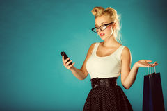 Pin up woman with shopping bag and phone. Royalty Free Stock Photography